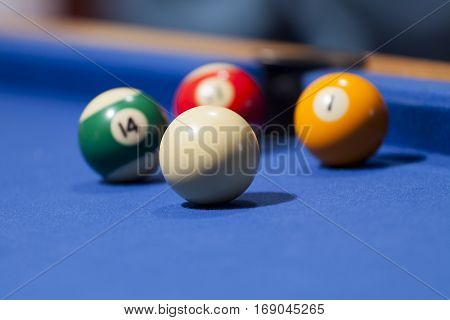 White, yellow, green and red billiard balls in a pool table. Focus on white billiard ball