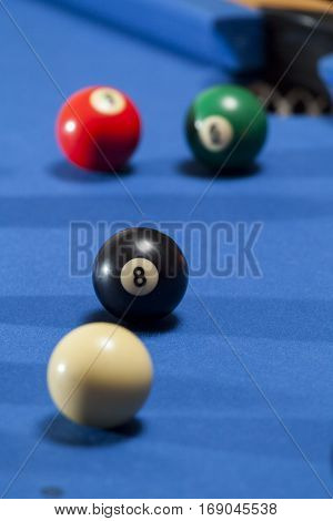 White, black, green and red billiard balls in a pool table. Focus on black billiard ball