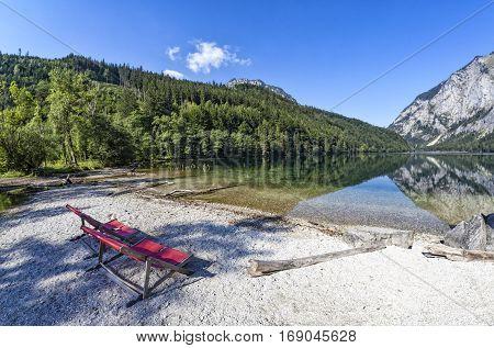Two red deck chairs on Lake Leopoldsteiner near Eisenerz in Styria Austria