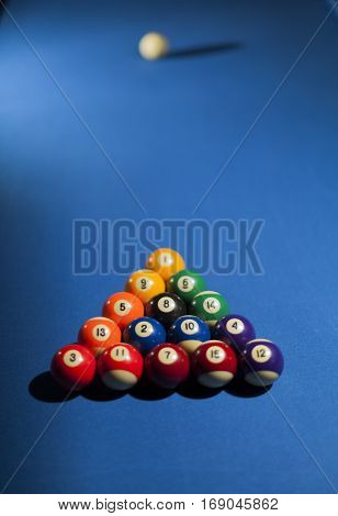 Pool billiard balls in commonly used starting position. Focus on black billiard ball