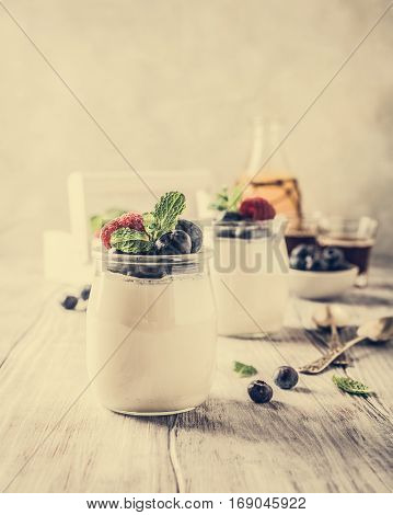 Natural yoghurt with berries on light gray background. Copy space. Healthy breakfast concept. Retro style toned.