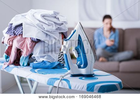 Lazy careless housewife on the couch at home and a pile of laundry on the ironing board on the foreground boring household chores concept