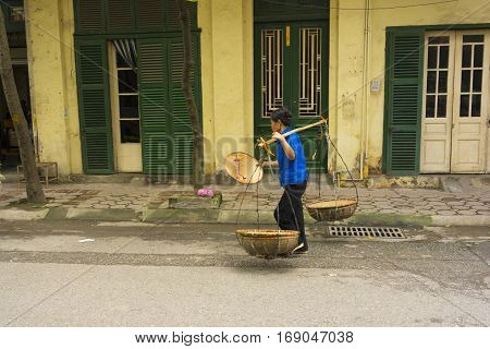 Hanoi, Vietnam - April 13, 2014: Unidentified vendor goes home with the empty baskets over old house on Hanoi str, Vietnam