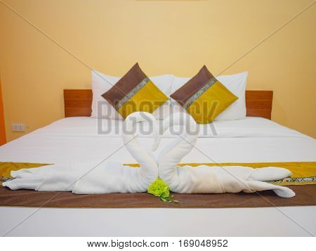 closeup of the fold towel as a swan kiss each other with white pillow and blown pillow on the white bed in bedroom