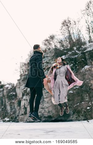 Beautiful couple levitates above the frozen lake. Guy and a girl are jumping of happiness among high rocks