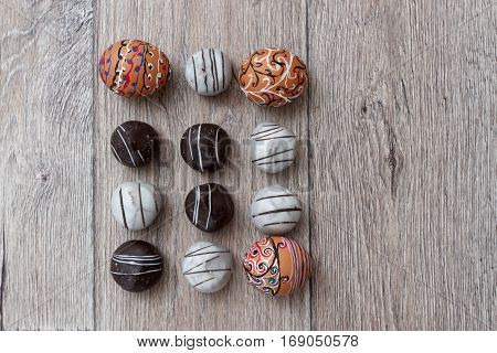 Handmade colorful painted easter eggs with chocolate candies against wooden background close up horizontal top view with coy space. Easter greeting card concept