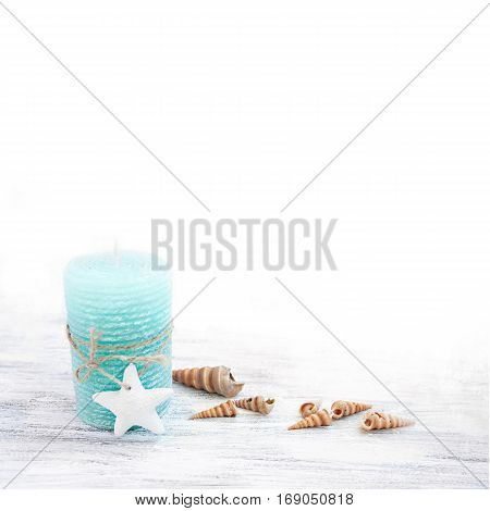 Soft light background with turquoise candle, starfish and seashells on brushed table