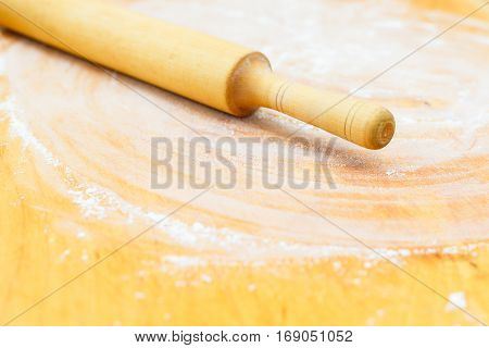 Wood chopping board with wheat flour and rolling pin on kitchen