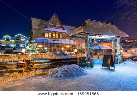 ZAKOPANE, POLAND - DECEMBER 30, 2016: Wooden architecture of Zakopane at snowy night, Poland. City center of Zakopane is the main shopping area with pedestrian promenade in Tatra mountains.