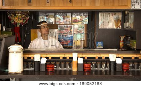 TOKYO-JAPAN, 27 June 2016: Japanese man standing in his restaurant at tsukiji fish market in Tokyo, japan. The biggest wholesale fish and seafood market in the world.