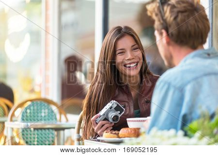 Couple at cafe lifestyle. Young tourists eating breakfast at restaurant table outside sidewalk terrace at parisian bistro in european city. Asian woman traveler with vintage camera. Europe tourism.