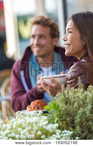 Happy people eating brunch at cafe. Young couple hipsters drinking coffee at restaurant table outside sidewalk terrace at parisian bistro in european city. Asian woman happy with boyfriend or friend.