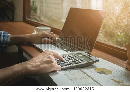 close up Business man using calculator with laptop and stock maket chart on wood desk. vintage filter effect