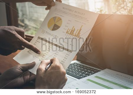 Close up Business man pen pointing stock maket with partner working at the office. analysis document and using laptop