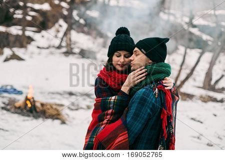 Guy and girl at a picnic. They bask with blanket near the bonefire. hey are happy and are pleased of life