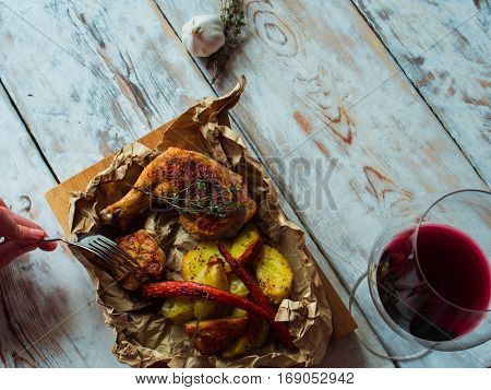 Chicken legs grilled on a wooden board with vegetables. Dinning concept.