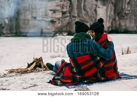 Couple sitting near a bonefire. They are covered with a warm blanket because the is cold