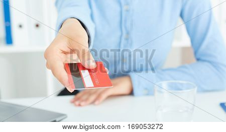 Closeup of red credit card holded by hand. Focus on hand.