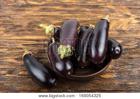 harvest of eggplant in a clay plate on an old dark wood table