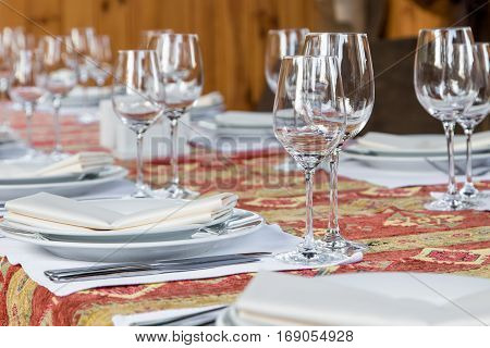 Table served with dishes close up. Ethnic table cloth served with glasses plates and cutlery