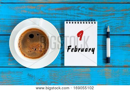 February 9th. Day 9 of month, Top view on calendar and morning coffee cup at workplace background. Winter time.