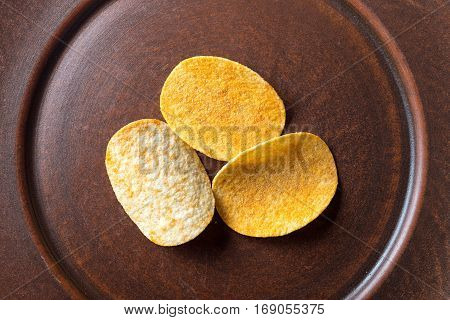 potato chips in an earthenware dish plate stands on a blue wooden background. beer snack unhealthy eating