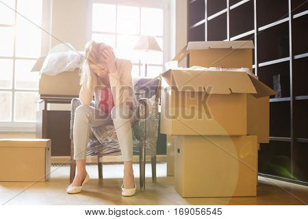 Full-length of frustrated woman sitting by cardboard boxes in new house