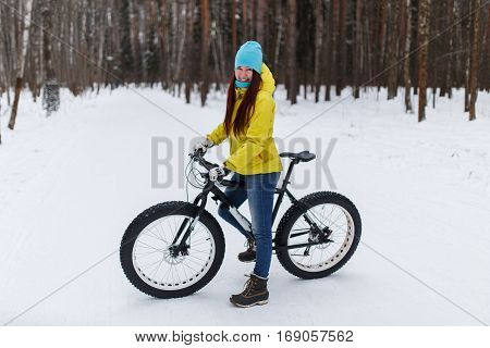 Photo of young girl in yellow jacket at winter cycling