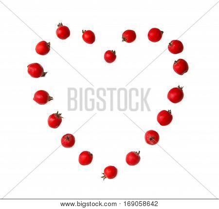 Hawthorn berries in heart shape on white