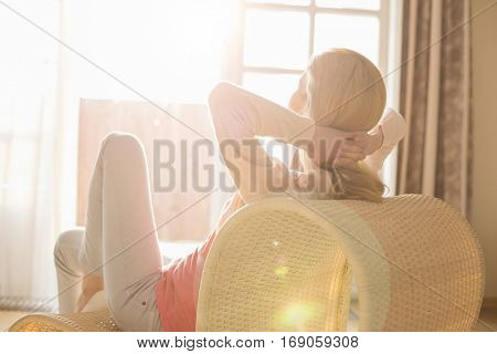 Rear view of woman relaxing on chair at home