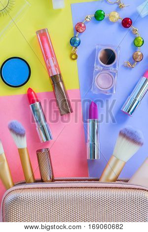Colorful make up products with pursue pop art top view flat lay scene