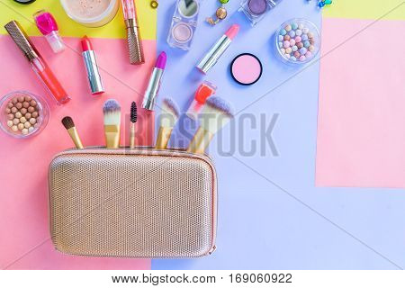 Colorful make up products with golden pursue close up pop art top view flat lay scene