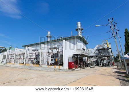 High-voltage power transformer in industrial power plant with blue sky