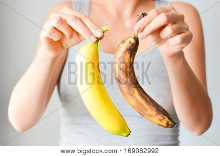 Fresh and overripe bananas on woman hand