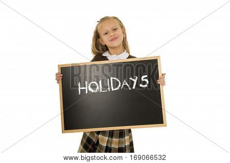 7 8 years old little beautiful blond schoolgirl smiling happy and cheerful holding and showing small blackboard with text holidays in end of school and education concept isolated white