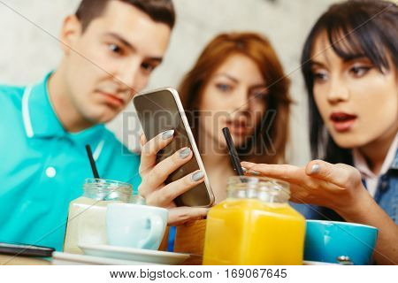 Young group of people looking at phone and they are shocked