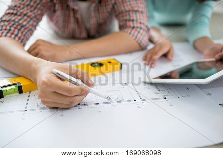 Attractive young asian adult couple looking at house plans.