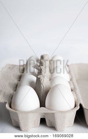 ten white egg in paper box- isolated on white background