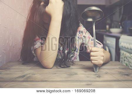 Kitchen ware on woman hand on wooden table