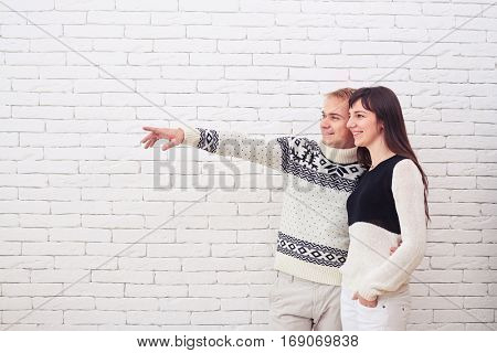 Side view of happy couple pointing sideway to empty copy space. Married couple. Husband embracing wife while pointing sideway