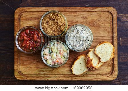 Close-up of healthy and nutritious dinner consists of meals in jars standing on the cutting board. Slices of baguette