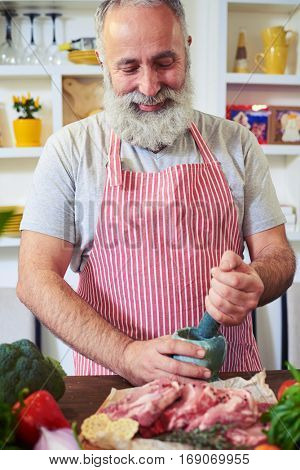 Mid shot of a man grinding spices on a cutting board. He wears stripped red and white apron standing isolated in the kitchen. Trying to prepare a nutritious dinner