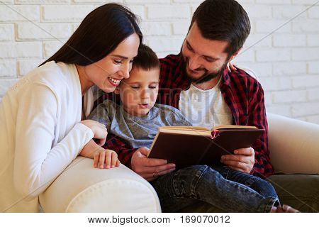 Close-up of happy family moments. Parents encourage child to read the book while spending time together in the living room