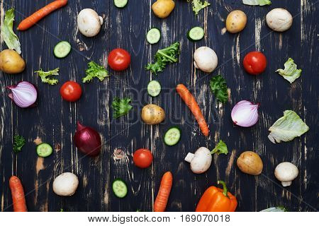 Top view of vegetables evenly arranged over wooden flat layout. Assortment of fresh vegetables. Fresh organic products. Colorful vegetables background