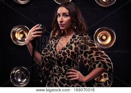 Mid-length shot of exhilarated young female singer in a chiffon leopard dress isolated over spotlight. Using studio microphone and posing at the camera