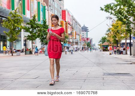 Asian woman walking downtown on Wangfujing shopping street in Beijing, China, using phone app to find directions or text online. Happy Chinese woman texting on mobile sms smartphone.