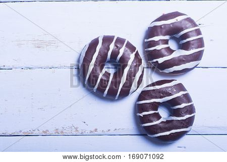 assorted donuts with chocolate frosted on wooden background