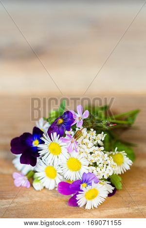 Bouquet of colourful garden flowers on wooden table with copy space. Selective focus.