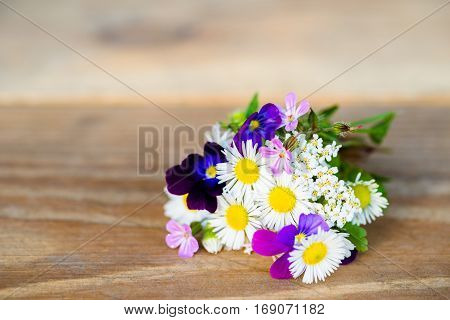 Bouquet of colourful garden flowers on wooden table with copy-space. Selective focus.