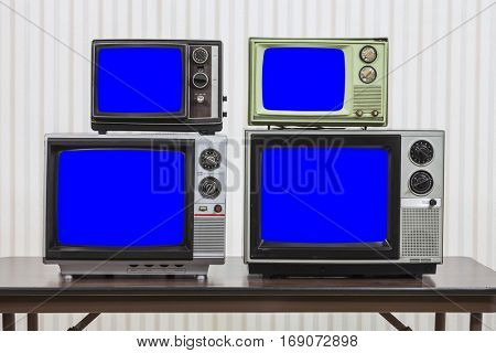 Four vintage televisions on table with chroma key blue screens.